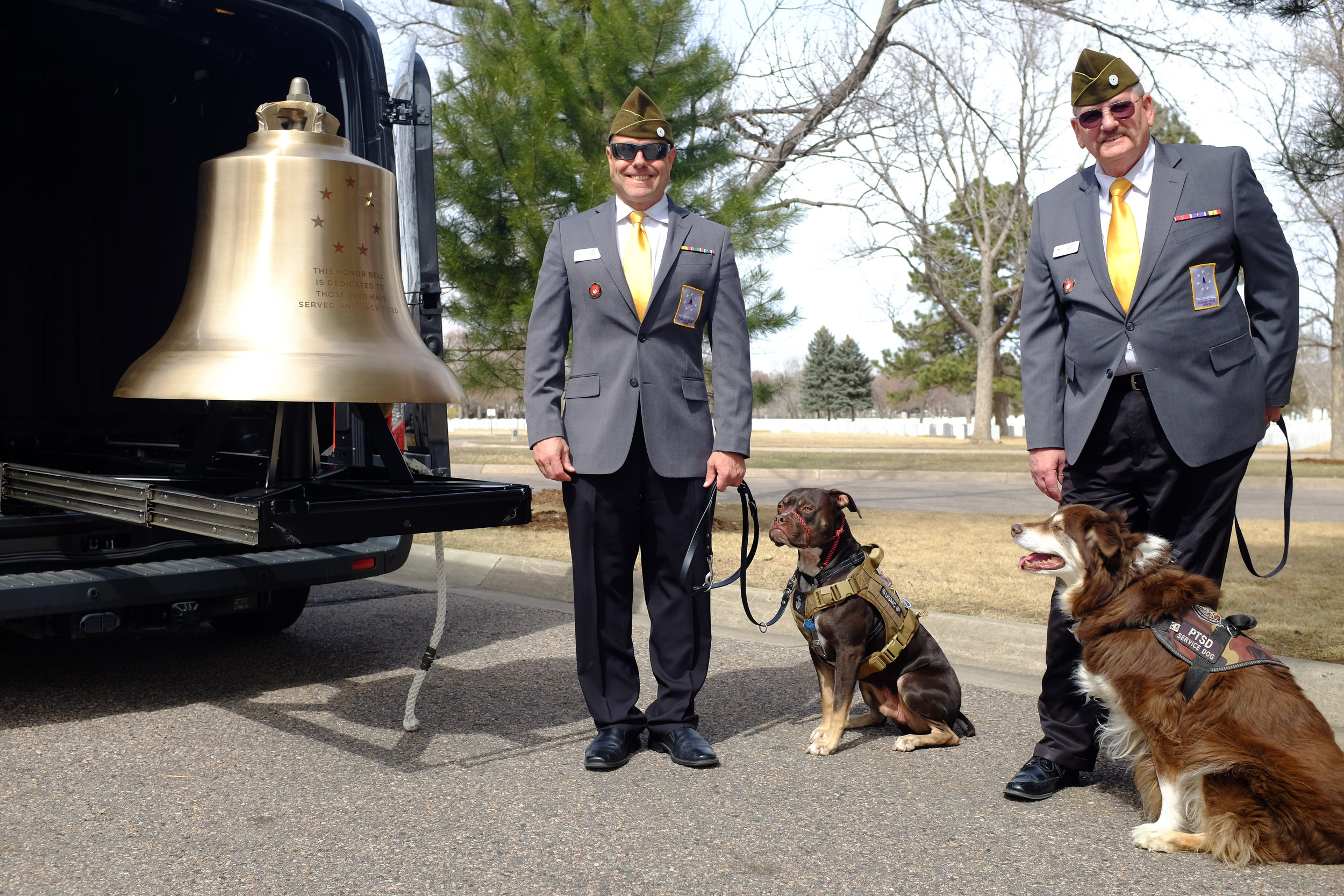 Chris Boyer with Noodle, and Ric Payne with Jack, on a recent afternoon at Fort Logan National Cemetery with the Honor Bell.