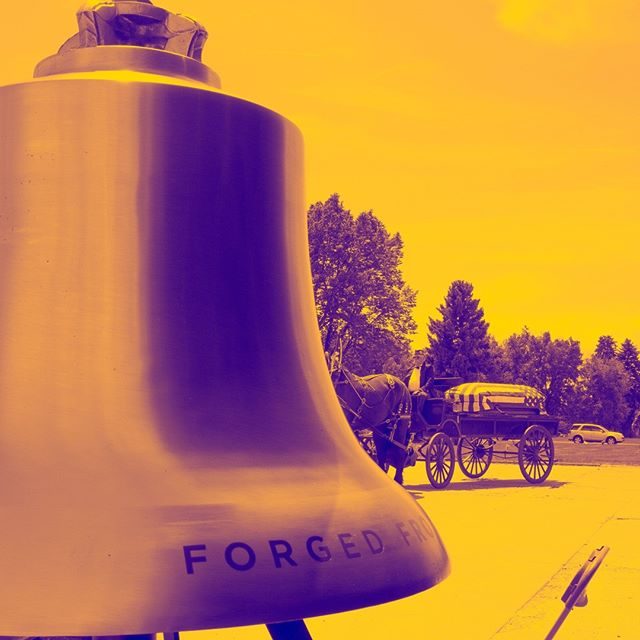 The Honor Bell, standing silent while a flag-draped casket is pulled on a caisson by a team of horses during a Memorial Day service at Crown Hill cemetery in Wheat Ridge, Colorado, in 2016. While the Honor Bell is tolled only for funeral honors at Fort Logan National Cemetery, it tolls at memorial services throughout Colorado when not in service during the week.