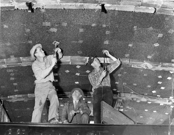 President Truman looks on as Workmen install Cork Insulation to the White House Ceiling