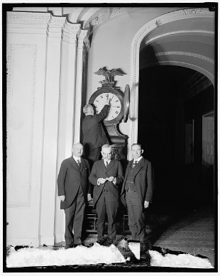 Senate Sergeant at Arms Charles Higgins turns forward the Ohio Clock for the first Daylight Saving Time, while Senators William Calder (NY), William Saulsbury, Jr. (DE), and Joseph T. Robinson (AR) look on, 1918. credit: Senate Historical Office