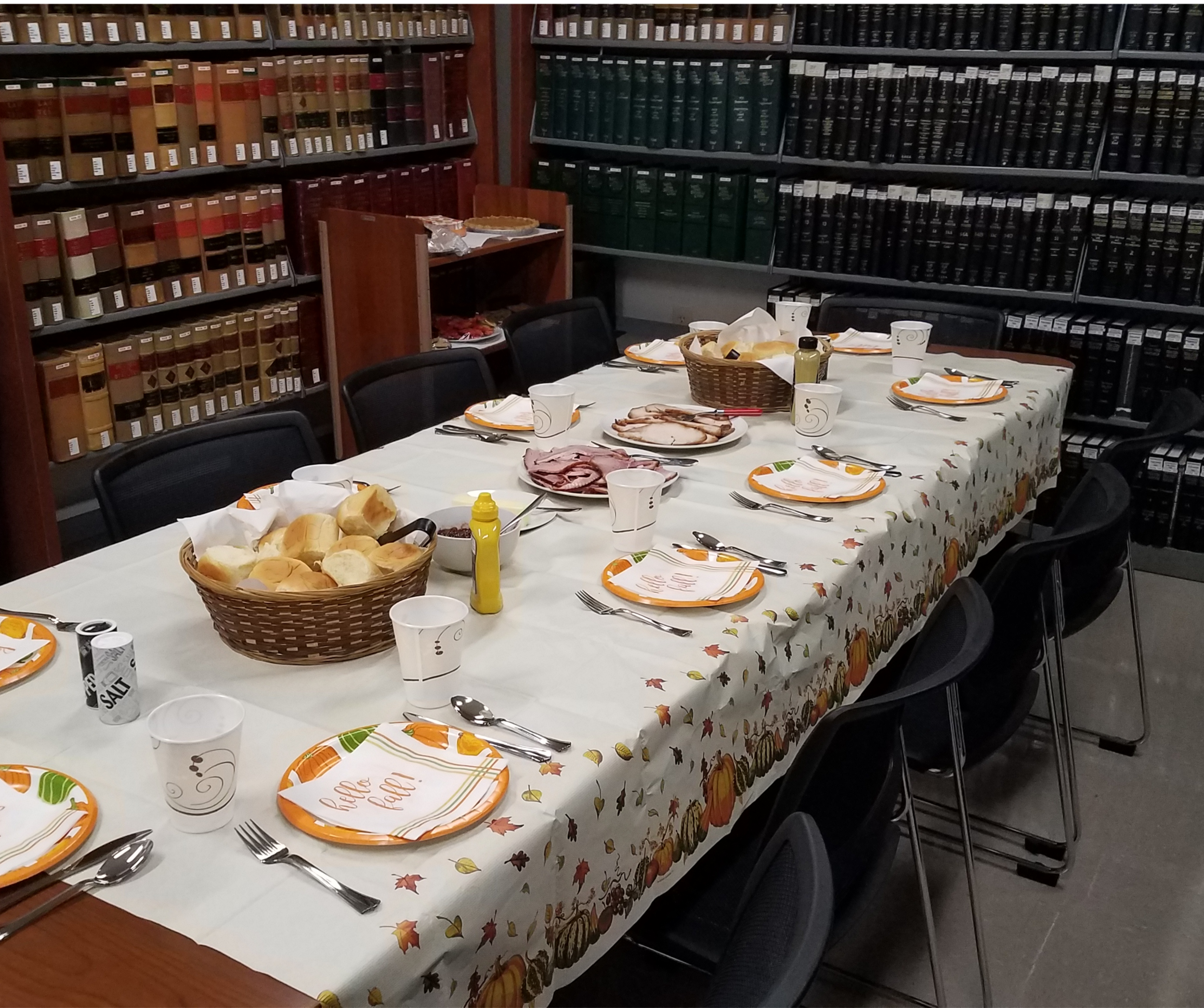 Table setting for Harris County Law Library staff Thanksgiving potluck among historical statute books.