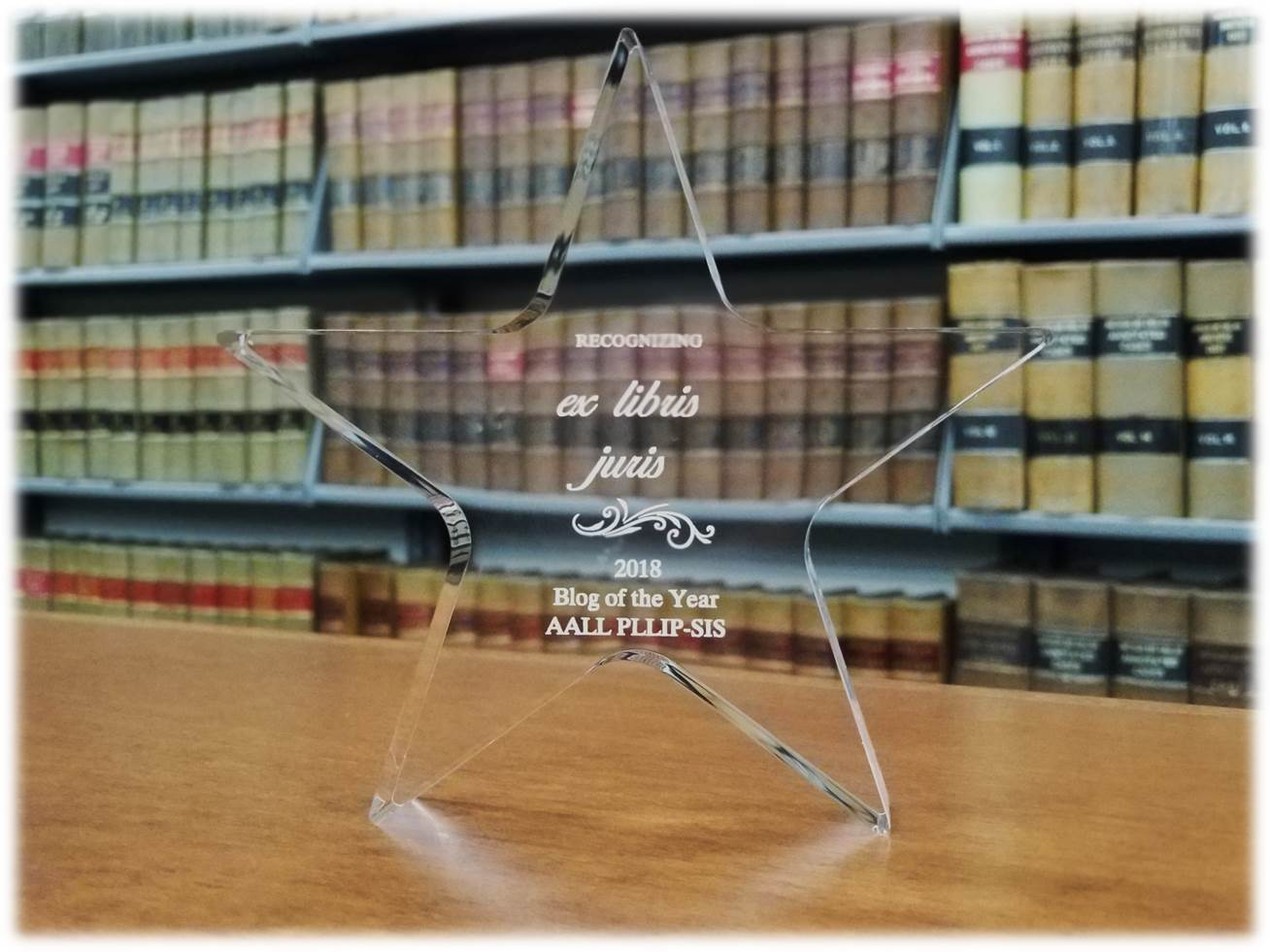 "Acrylic star in front of bookcase inscribed, ""Recognizing ex libris juris, 2018 Blog of the Year AALL PLLIP-SIS"