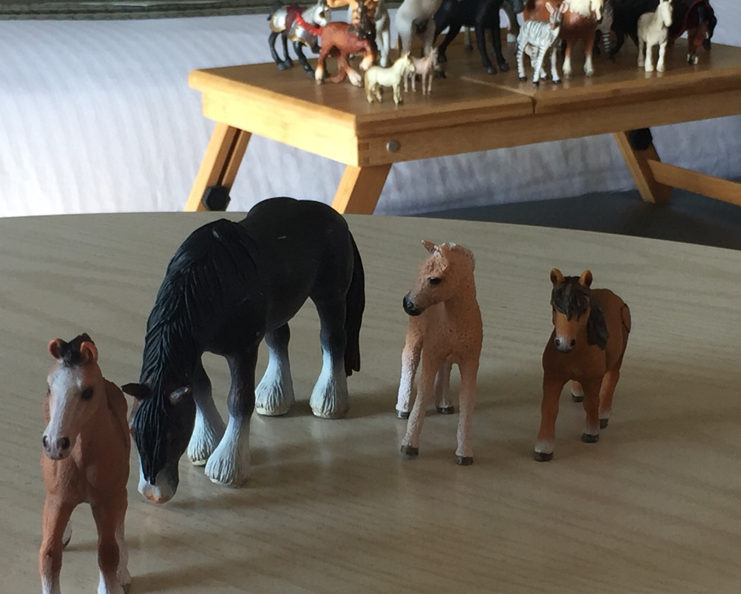 A family constellation using toy horses: older sister in front, mom behind, younger sister and brother on the right.