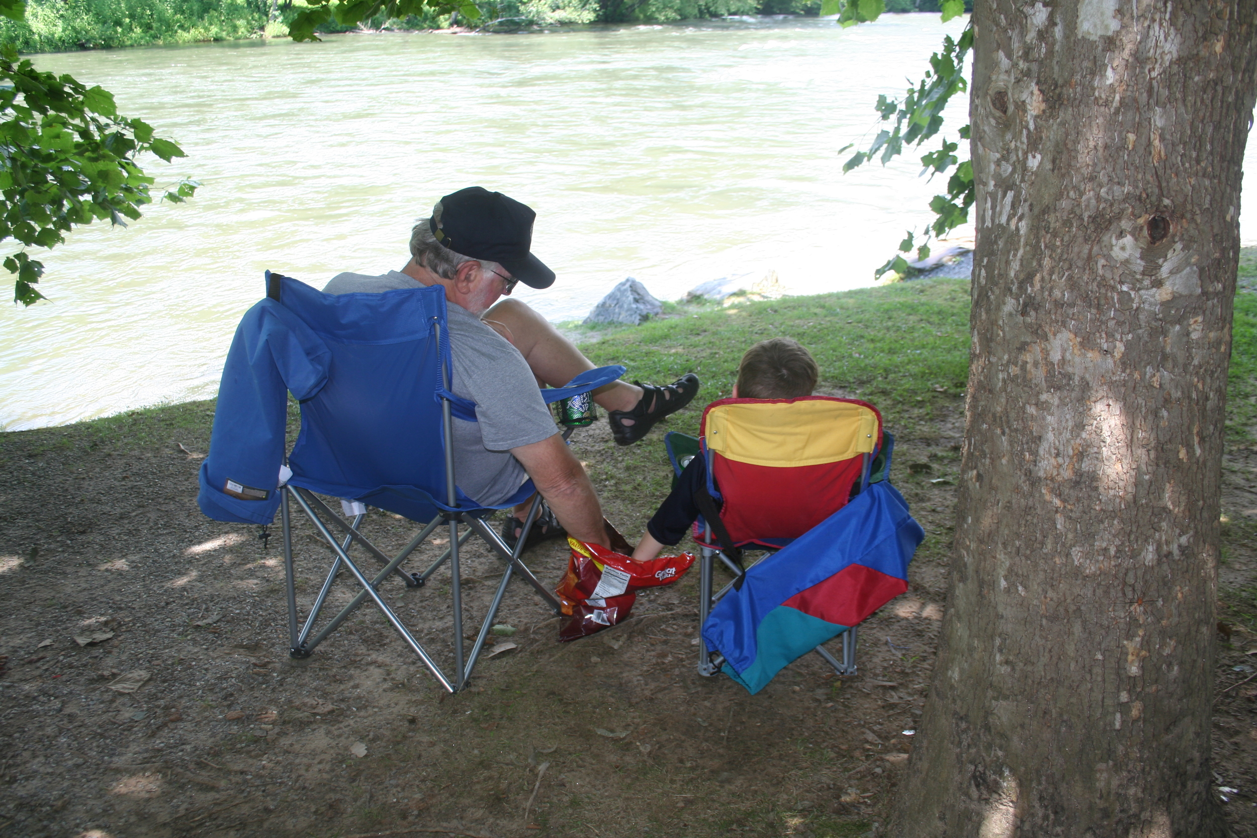 Carl and Dewey share chips at the river.