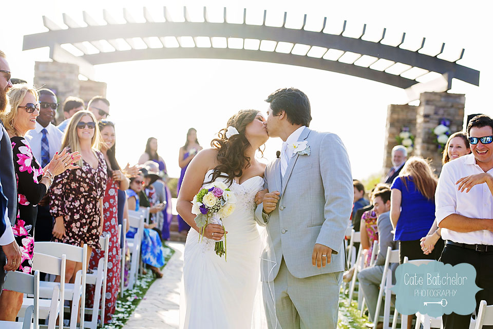 Sneaking in another kiss as husband and wife, as their guests cheer on!