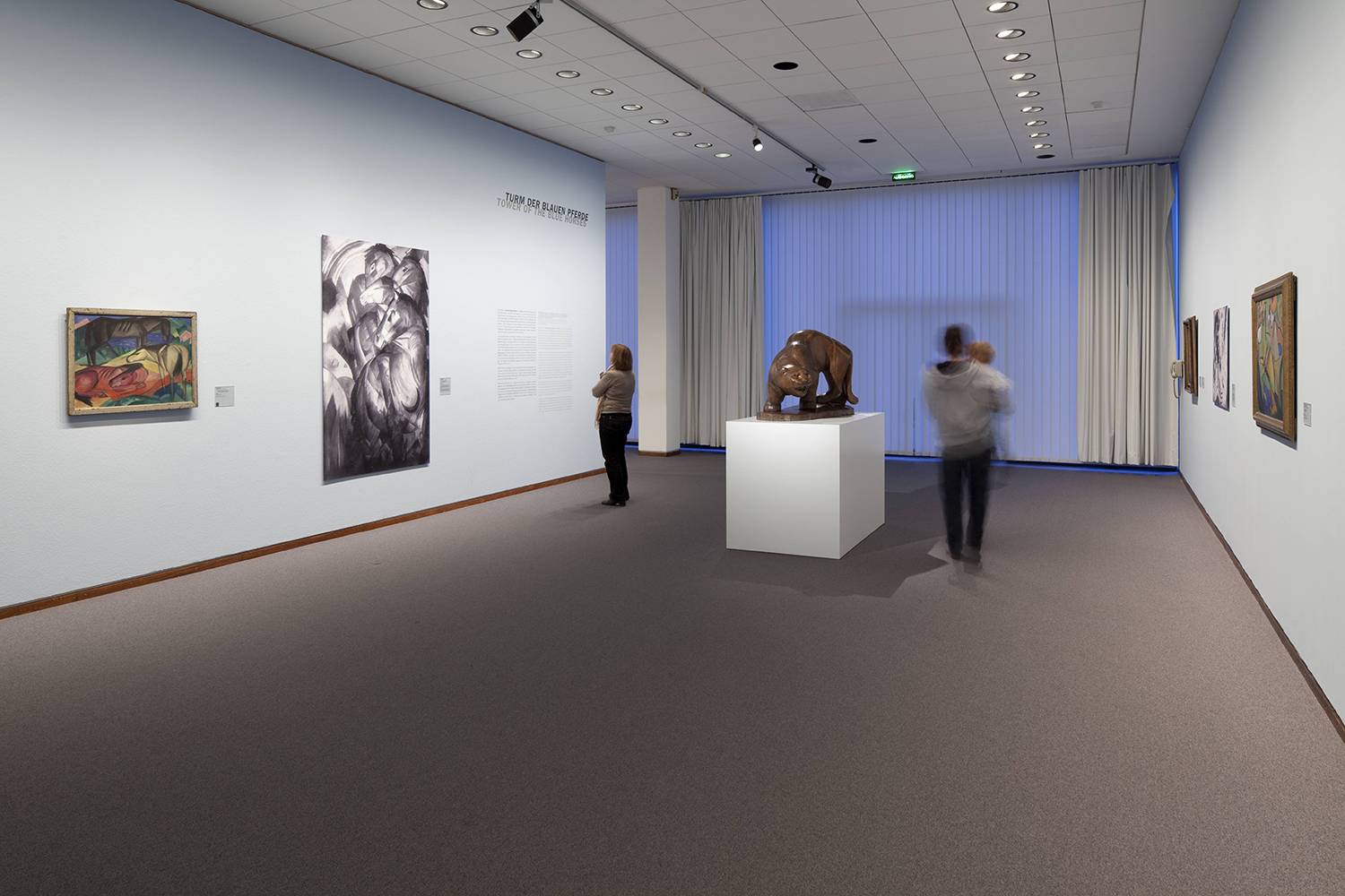 "Photograph of Tower of Blue Horses on display in Modern Times, 2010. Photo by Simon Vogel Wall tag of black and white photograph: Franz Marc 1880 München − 1916 Verdun Tower of Blue Horses 1913 Oil on canvas Acquired in 1919 from the artist's widow; exhibited until 1936 in the Kronprinzen-Palais; seized in 1937 and displayed at the ""Degenerate Art"" exhibition in Munich; removed again from the exhibition after several days; confiscated before 1940 by Hermann Göring; lost since 1945"