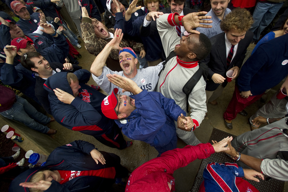 """University of Mississippi football fans Darin Farley (bottom) and Todd Morris (top left) give the """"Land Shark"""" fin salute with Rebels defensive end Jason Jones in """"Whiskey Alley"""" during the team's Champions Walk parade through The Grove on the Ole Miss campus before the Rebels take on Texas A&M University."""
