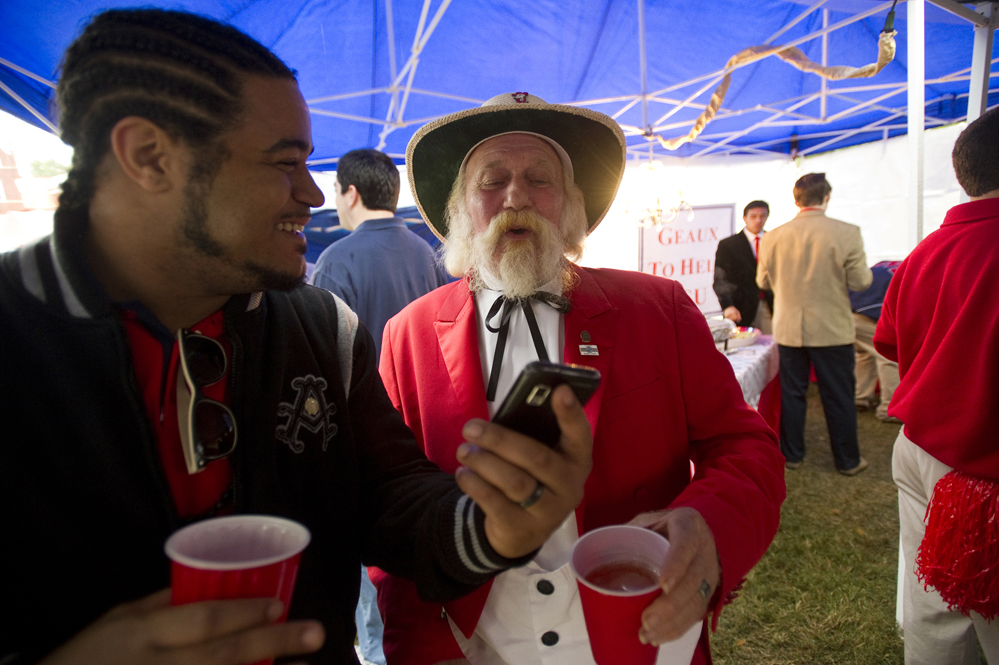 Demetrios Brown (left) shares a photo of his son with Butch Harris, dressed as former Ole Miss Mascot Colonel Reb, inside a tailgating tent at The Grove on the University of Mississippi campus before the Ole Miss Rebels take on Texas A&M University.