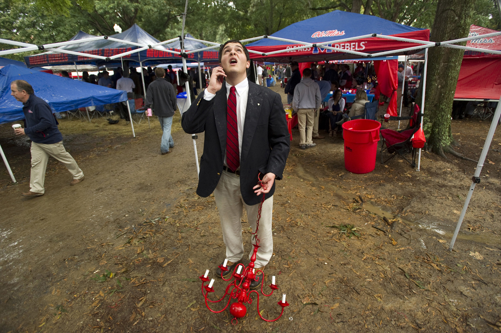 Nate Blumberg calls a friend to ask for advice on how to hang a chandelier from his tent's frame during tailgating at The Grove on the University of Mississippi campus before the Ole Miss Rebels football team takes on Texas A&M University.