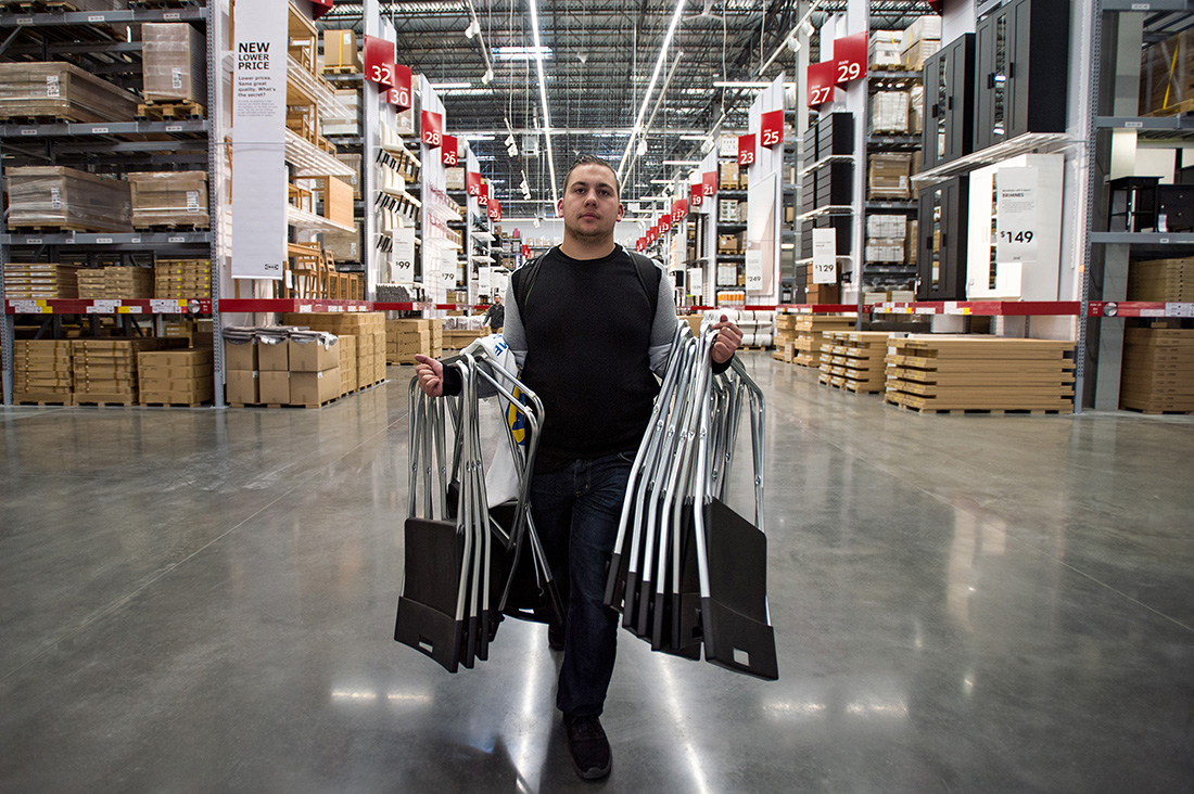 Jaylen Roach carries armfuls of stacking chairs as one of the first shoppers inside home furnishing retailer IKEA's new Memphis store during an event marking its grand opening.