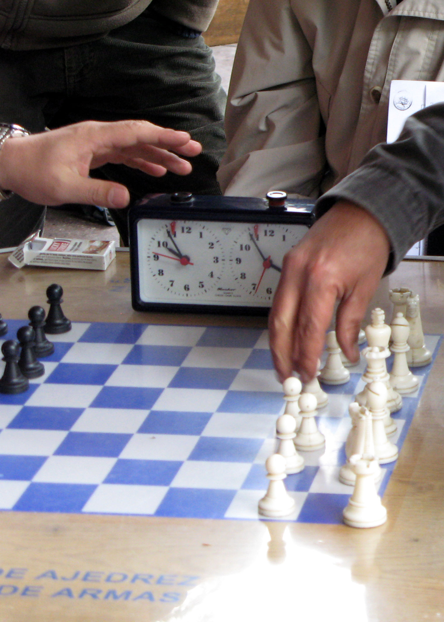 Finger on the timer as the opponent makes his move.