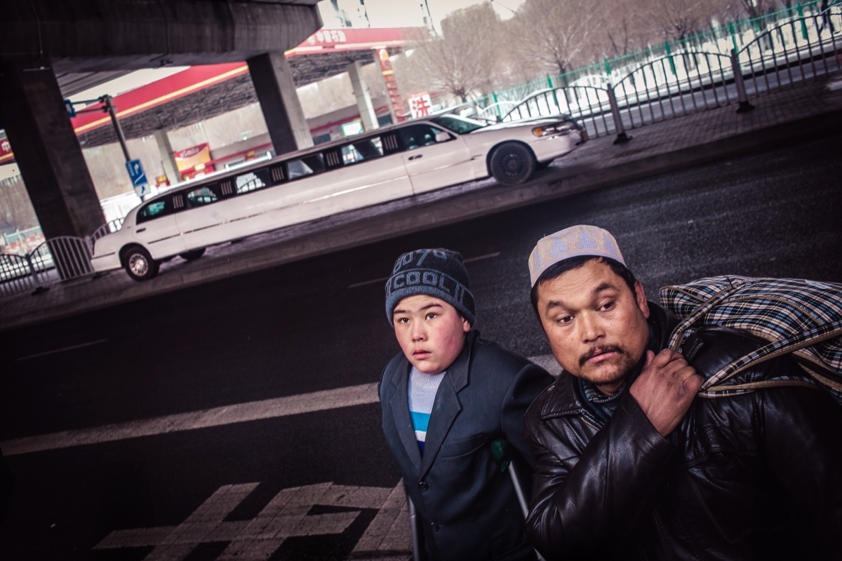 Uyghur young men cross the street in front of limousine that is used in marriage celebrations and other social events.