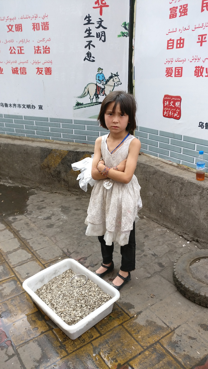 A Uyghur child sells sunflower seeds on the back streets of Ürümchi. Behind her propaganda posters from the Ürümchi Ministry of Culture describe the ideals of the political regime: civilization, harmony, prosperity, justice, rule of law, freedom, honesty, friendship, patriotism.