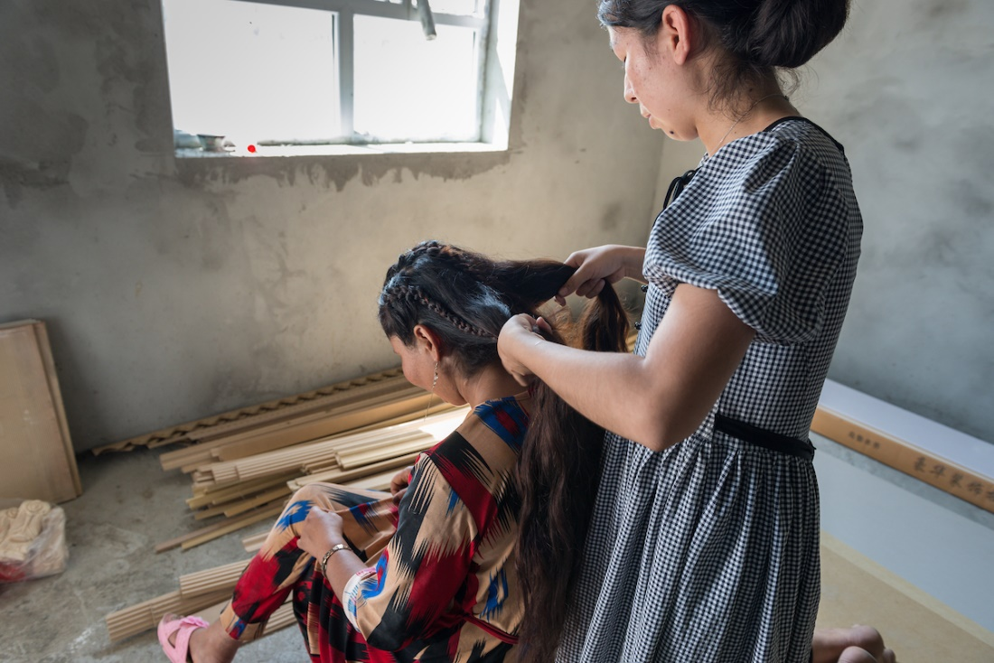 Gulnar begins to braid her friend's hair to soothe her crying during a very quiet private conversation in an unfinished room of the family's house.