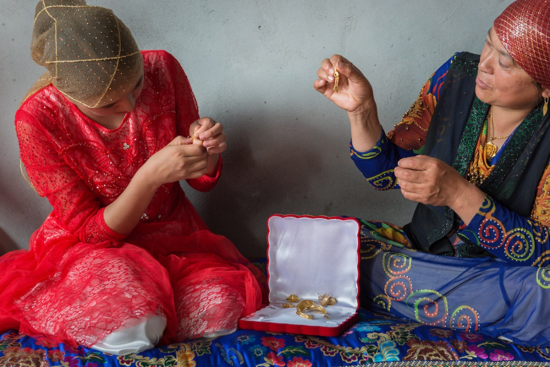 After days of celebrations, a Memetjan's bride is presented with gold jewelry in her husband's home.