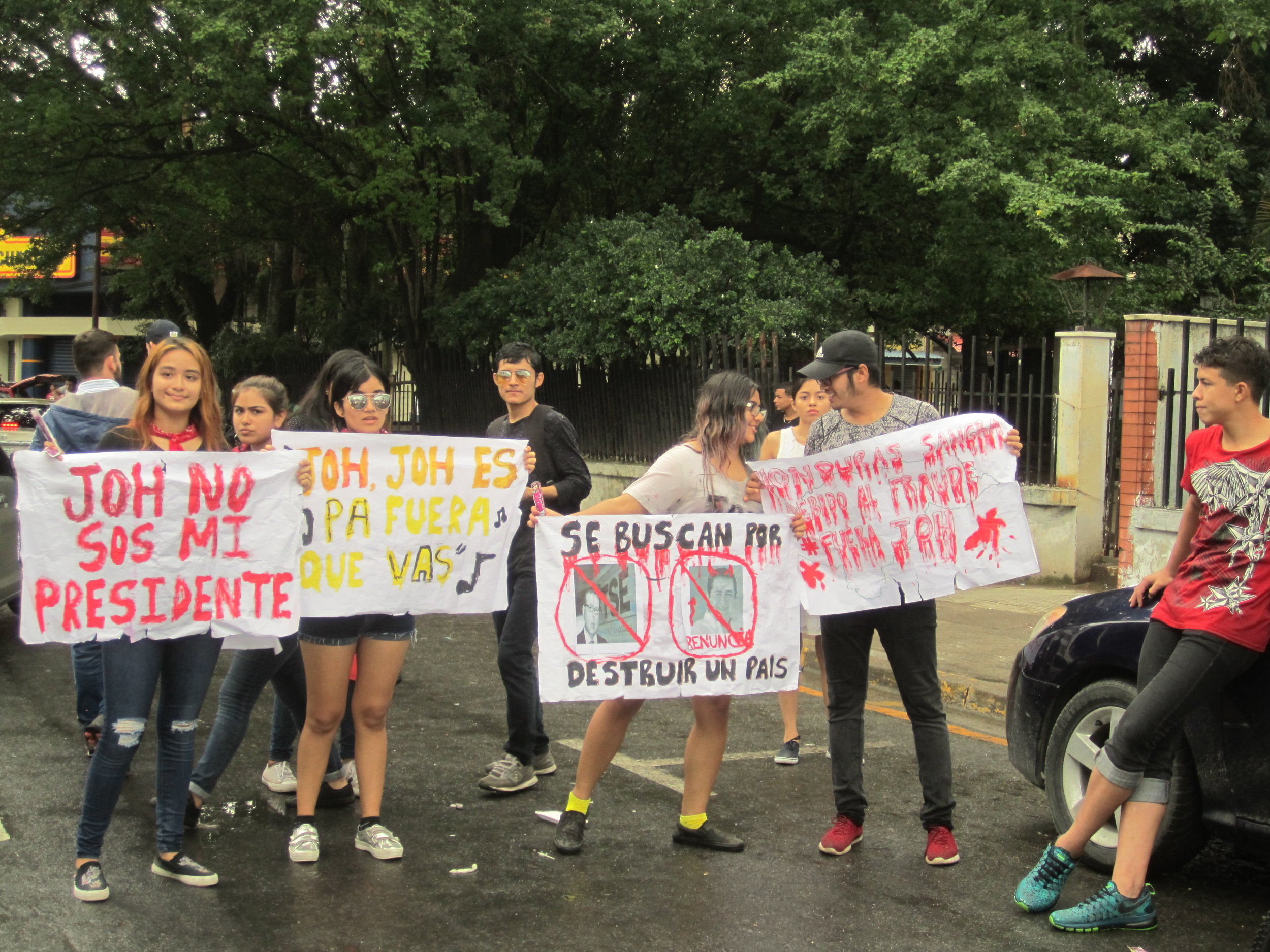 "San Pedro Sula, Cort  é  s. Sunday, December 3rd. Young people with signs that read (left to right)   ""  JOH you are not my president  ""; ""JOH you are leaving (with music notes to reference the popular song)""; ""wanted for destroying a country""; and ""Honduras bleeds because of fraud. Get out JOH."" Photo credits: Author."