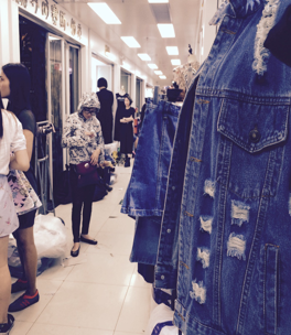 A young customer takes a break from the hustle that often characterizes this fashion market. Photo credits: Nellie Chu
