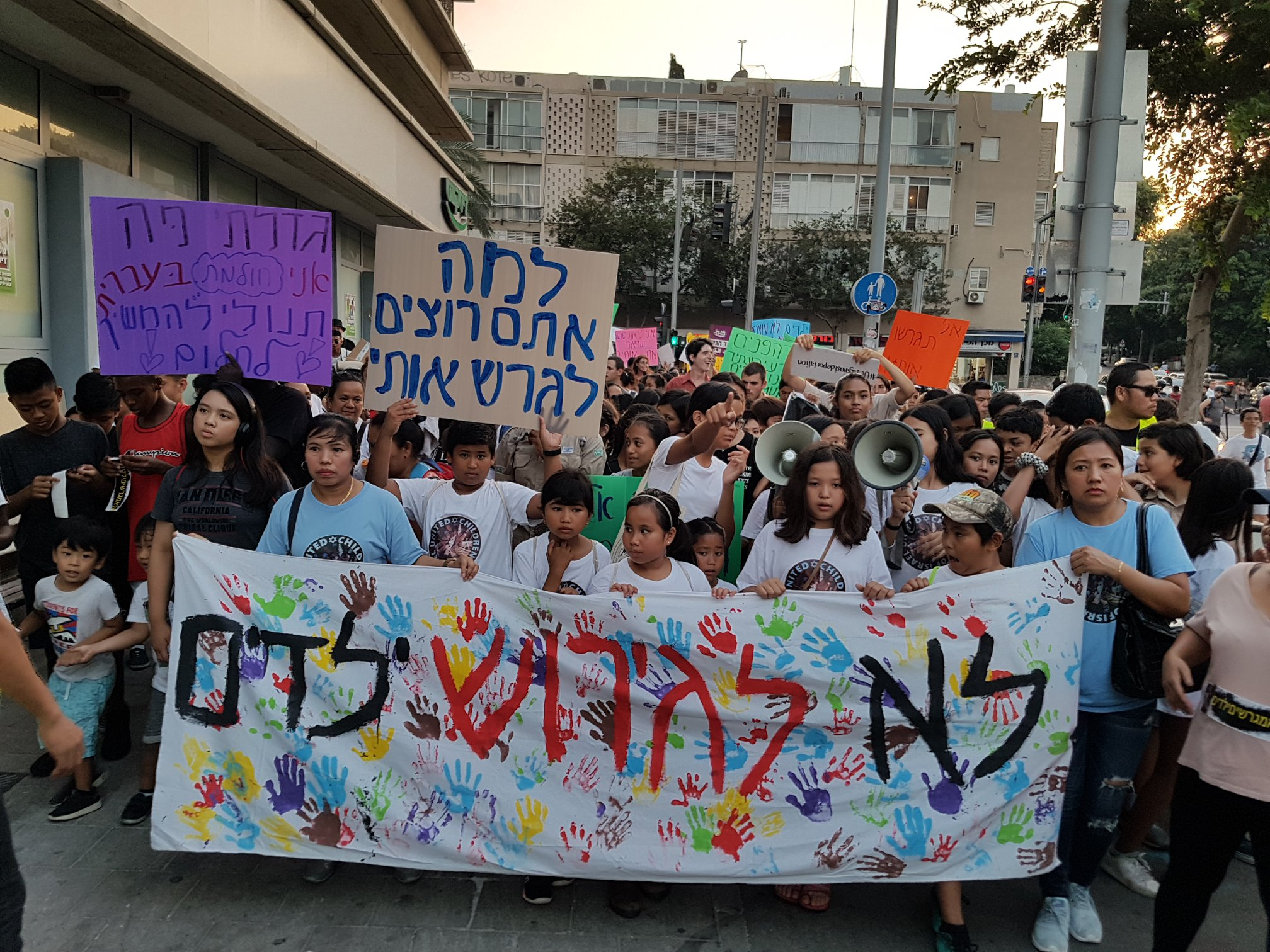 """Large Hebrew banner reads, """"Don't deport children."""" Smaller sign reads, """"Why do you want to deport me?"""" Source: United Children of Israel."""