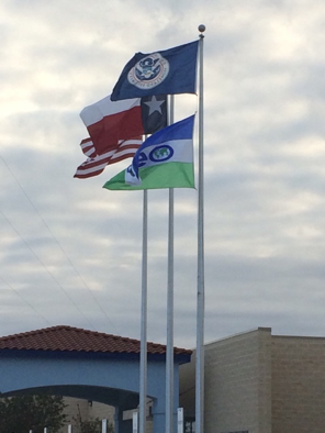 A GEO Group flag flies alongside the United States, Texas, and Department of Homeland Security flags at the immigrant detention center in Karnes, City, TX. Photo credit: Laurie Cook Heffron