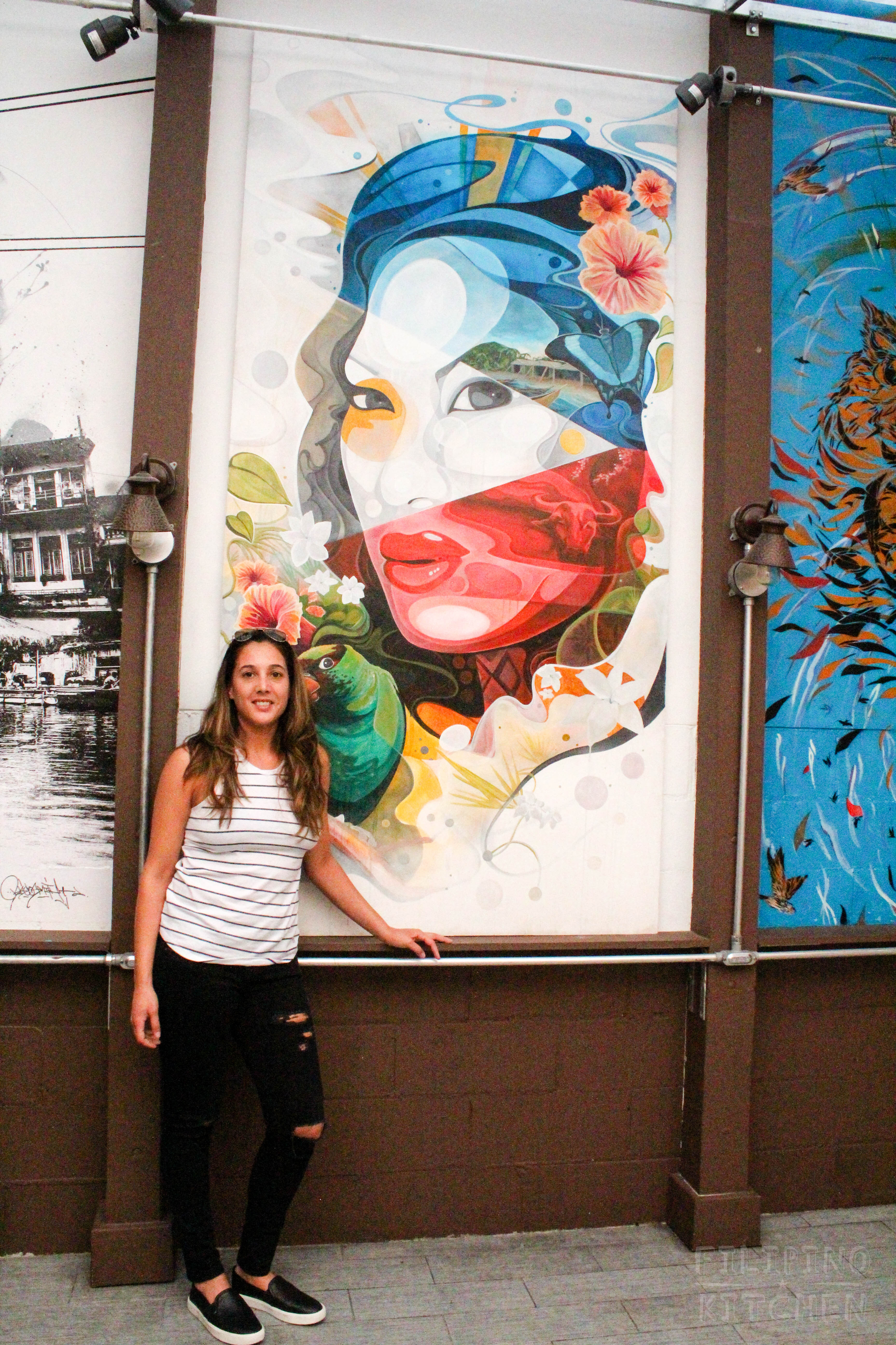 Chef Leah Cohen on the enclosed patio at her New York City restaurant, Pig & Khao. Mural by  BK .