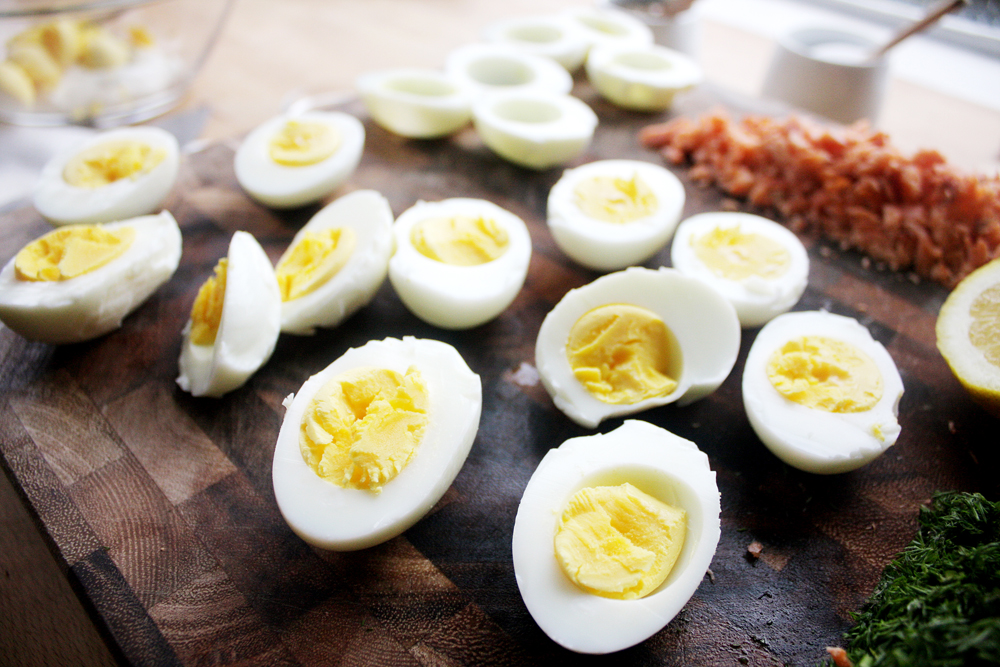 Gently cut your cooled and peeled eggs in half lengthwise, wiping your knife clean with a paper towel with every cut.
