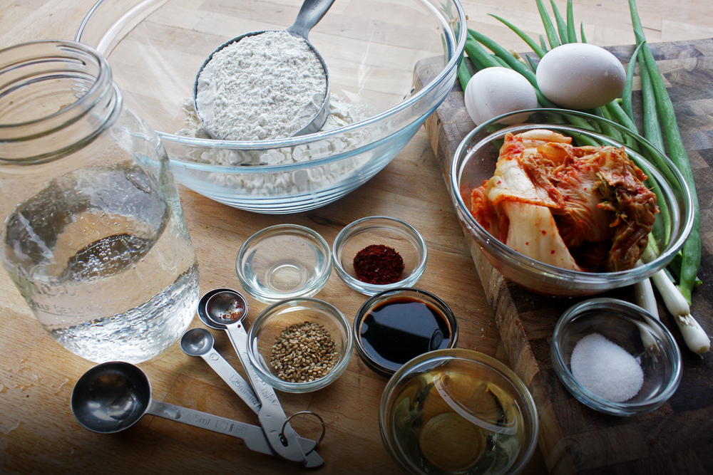 The ingredients:  kimchi , green onions, eggs, flour, club soda and salt. For the dipping sauce we have soy sauce,  rice wine vinegar ,  gochugaru , and  sesame seeds .