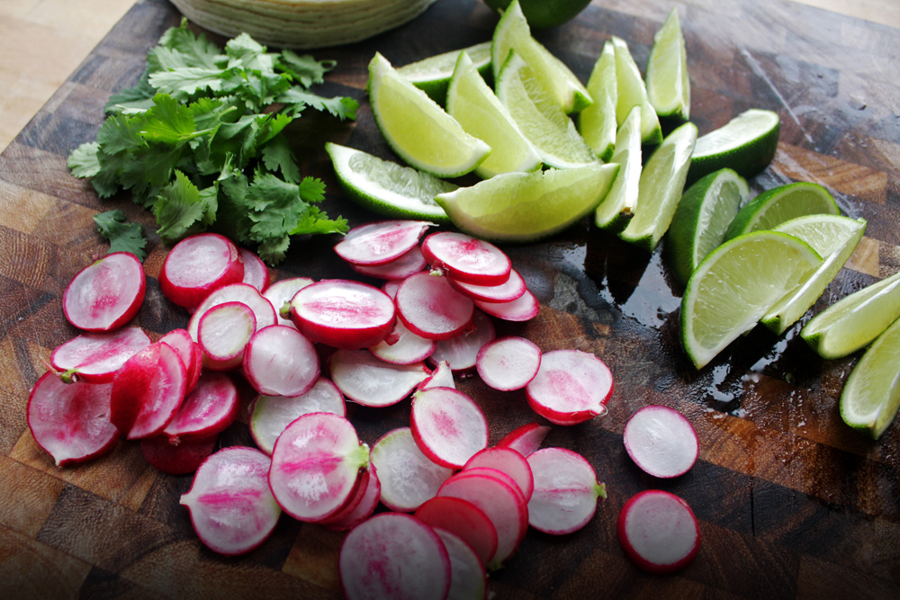 Prep the toppings by pulling the leaves off the cilantro stems (for easy eating), cutthe lime into wedges, and slice the radishes as thin as you can.