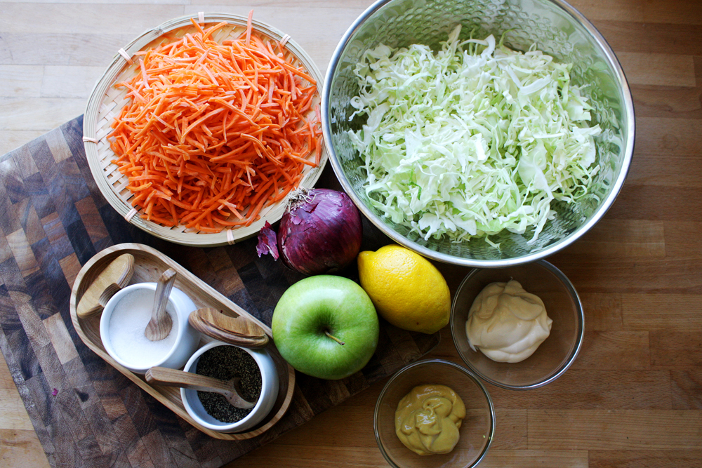 The ingredients: shredded cabbage, shredded carrots, green apple, red onion, lemon zest and juice, mayonnaise, honey mustard, pepper and salt.  A tip for the cabbage and carrots: buy them pre-shredded. They are easy to find prepped that way and are usually a couple of bucks.