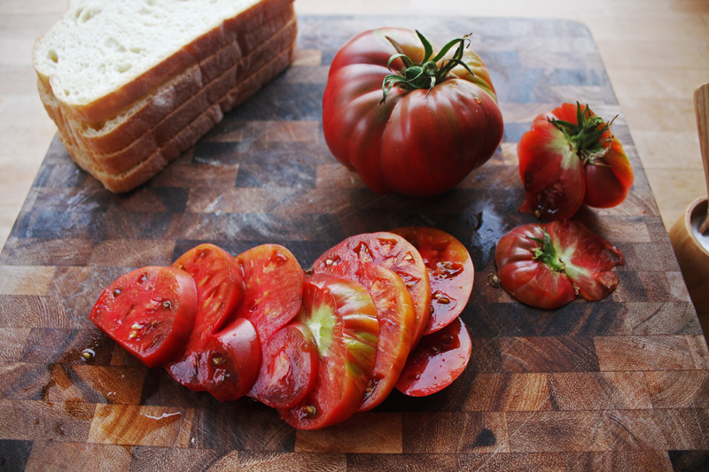 """Slice the tomatoes to about¼"""" in width. This variety of tomatoes usually grow in odd shapes, so first cut in half next to the stem, then do the same on the other side of the stem."""