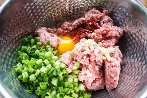 Combine the ground pork, green onions, garlic, gochugaru and 1 egg together. The egg is going to keep the pancake together.  Also, if you want to use beef instead go for it. Just add a large pinch of salt.