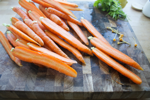 Wash and cut the tops off, then halve the carrots.