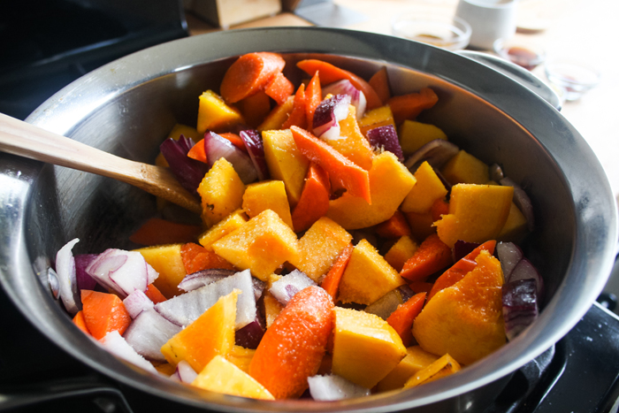 In a medium-high heat pot, put in some vegetable oil then start browning the pumpkin, red onion and carrots for about 10 minutes. Get the vegetables slightly tender.