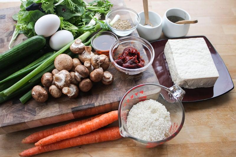 The ingredients: rice, firm tofu, carrots, cucumbers, mushrooms, green onions, fresh salad greens, eggs, gochujang, sesame seed oil, sesame seeds, vegetable oil, salt, and black pepper.