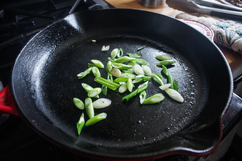 Take the mushrooms out then cook the bottom chopped bottom halves of the green onions for about 3 minutes, to take the bite out of them.