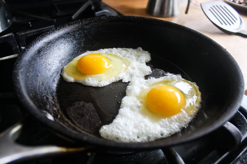 Turn your skillet to medium heat and add a little bit of vegetable oil. Carefully add the eggs, keeping the yolks intact. After the whites turn opaque, turn off the heat and cover with the lid for about 3-5 minutes.