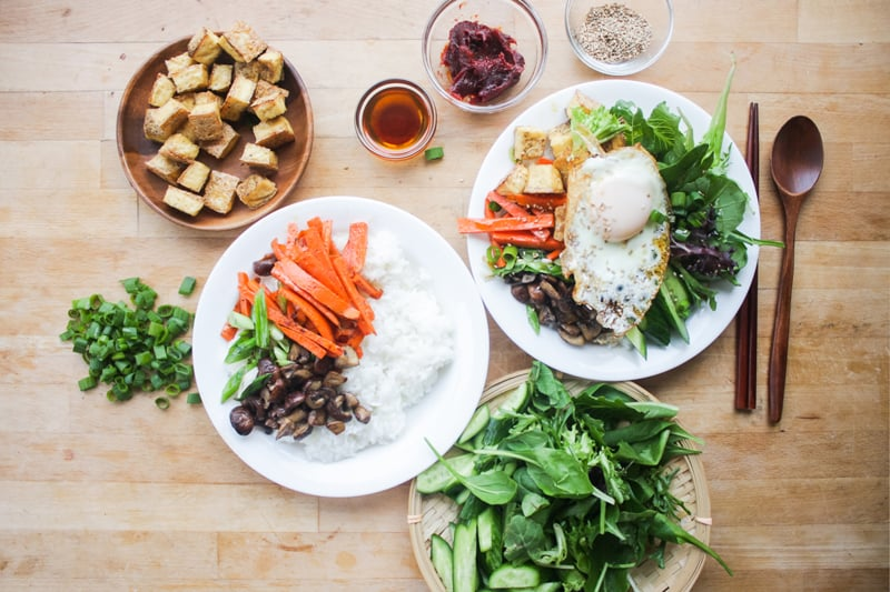 Assemble the bibimbap by putting the cooked rice on the bottom of a bowl. Individually add the carrots, mushrooms, cooked green onions, cucumbers, fresh greens, and baked tofu. Place the egg on top. Drizzle the sesame seed oil and add a dollop of gochujang. Sprinkle on sesame seeds and green onions.