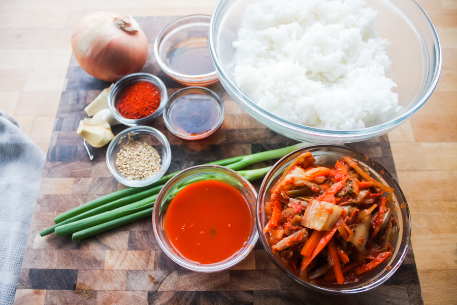 The ingredients: cooked white rice, kimchi, kimchi juice, sesame seed oil, fish sauce, gochugaru, white onion, garlic cloves, green onion, and sesame seeds.