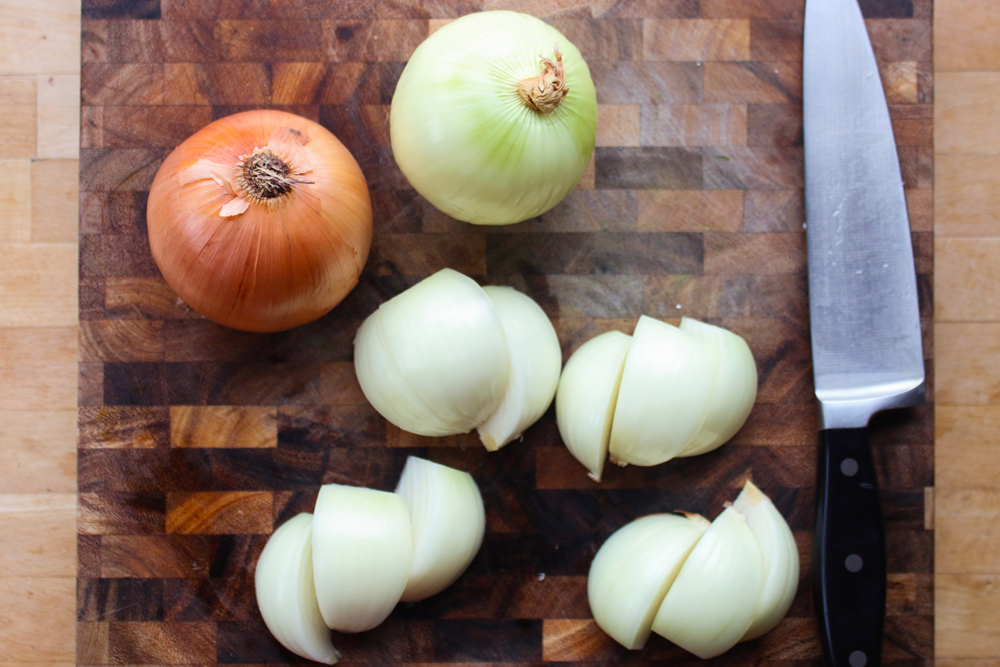 After the round tip is done marinating, peel the skin off the onions then cut into quarters. Leave as much of the core as possible so that the quarters stay intact.