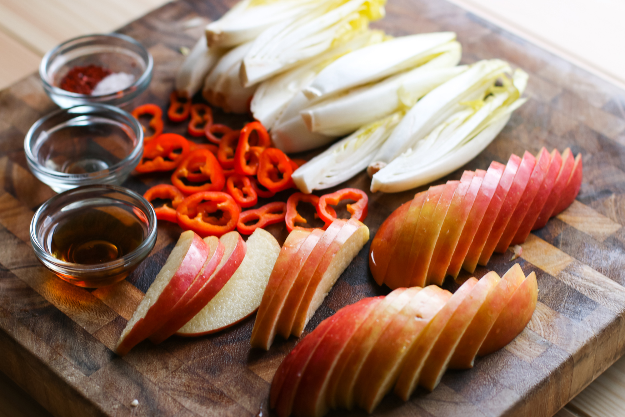 Quarter the endives. Thinly slice the chilis into round pieces. Cut large pieces around the core of the Fuji apple. Thinly slice while keeping the form of the piece intact, to be fanned in the salad.