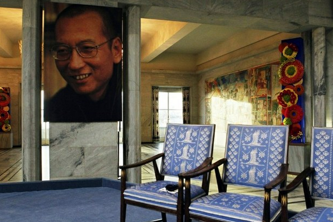 A portrait of imprisoned writer Liu Xiaobo hangs near the empty chair placed in his honour during the ceremony in Oslo, Norway in which he was awarded the Nobel Peace Prize in absentia on Dec. 10, 2010. Photo: AFP