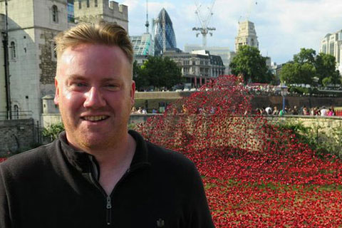 Paul Cummins standing in front of the  Blood Swept Lands and Seas of Red installation at the Tower of London