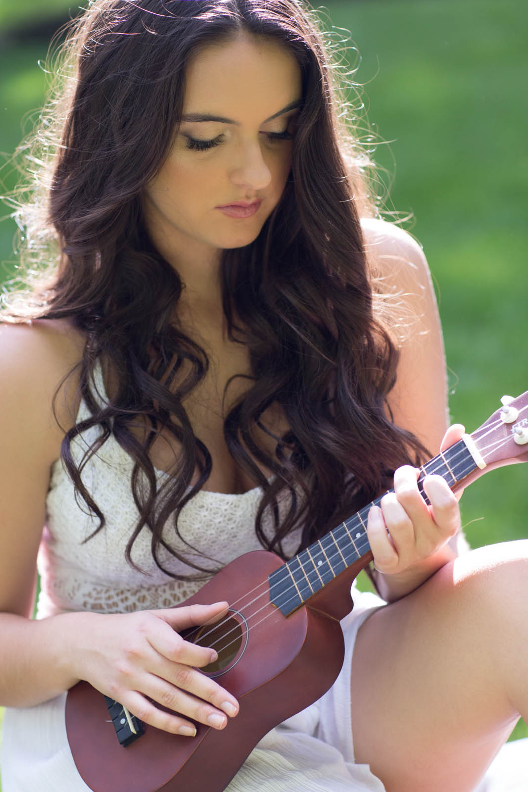Teen girl playing ukelele during senior pictures