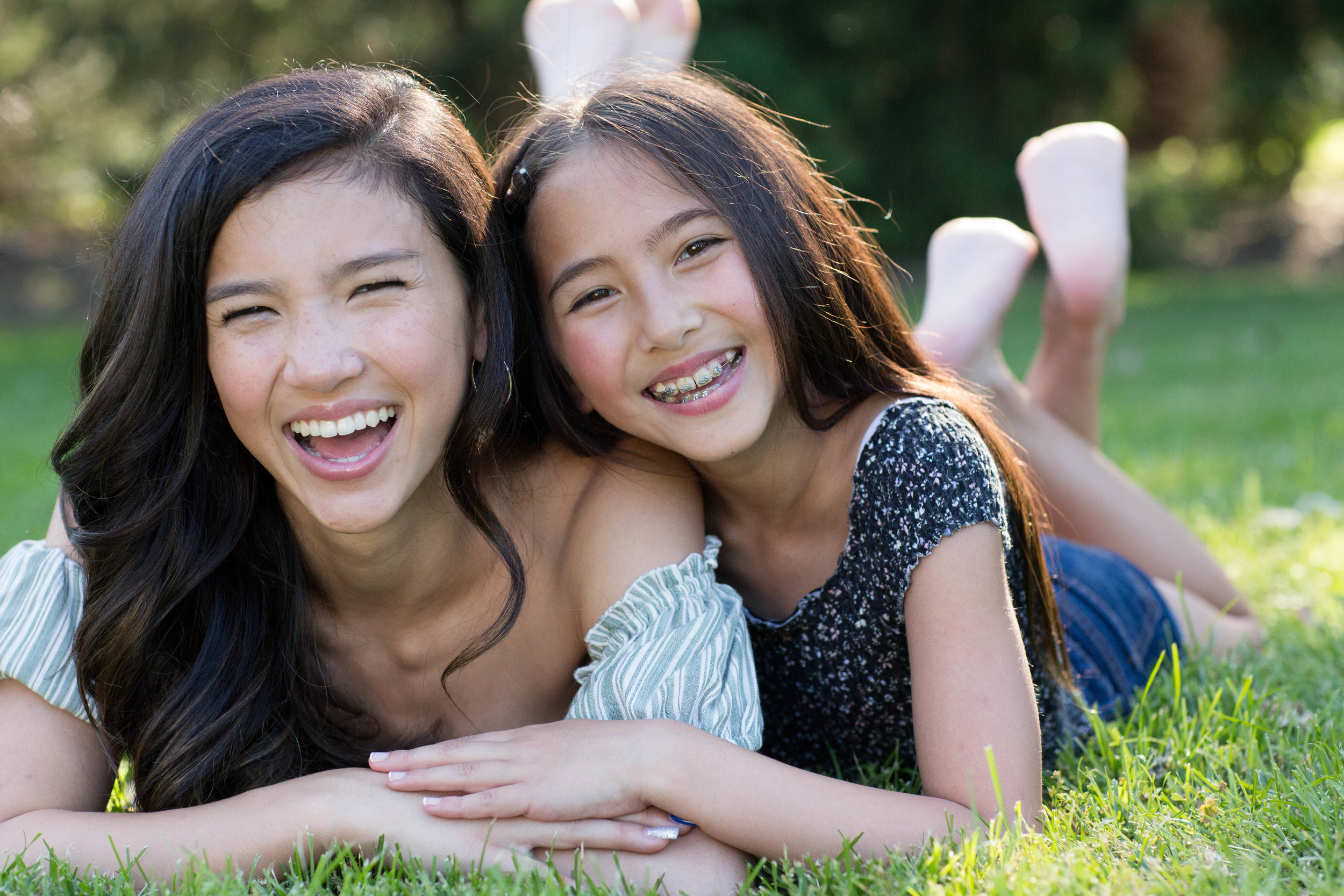 sisters laughing in grass