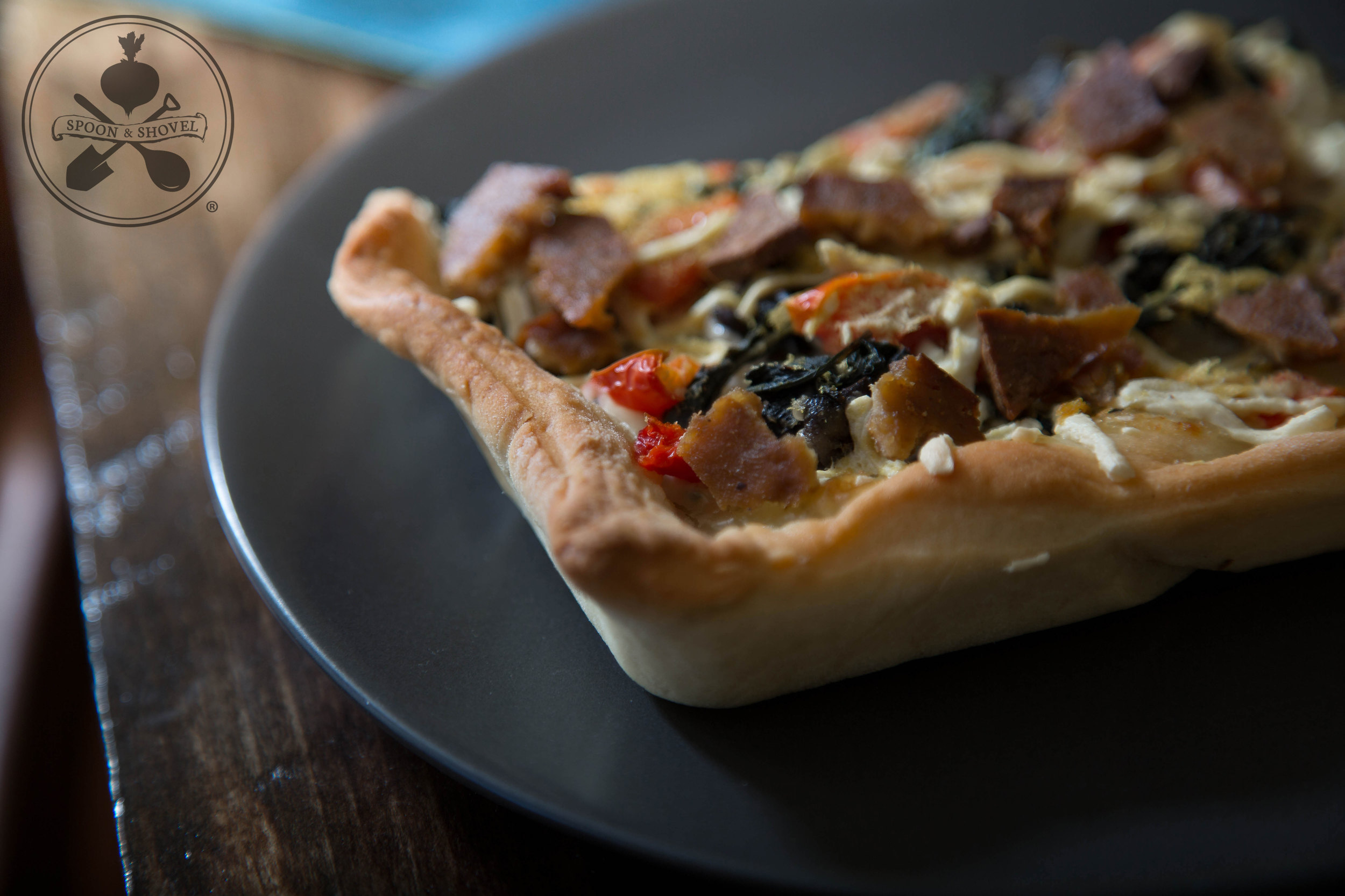 Vegan pizza with white sauce, spinach, veggies and tofu bacon from The Spoon + Shovel