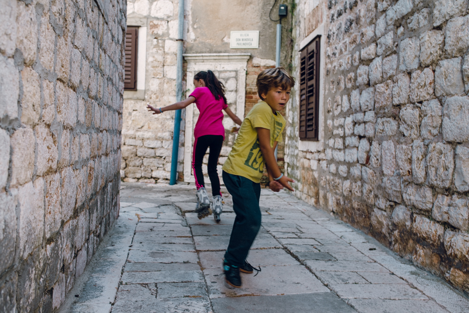 """A girl roller blades on the uneven ground. The boy was having a """"gun fight"""" with some of his friends - he was running with the girl but happened to do an about face right when I was snapping the photo."""