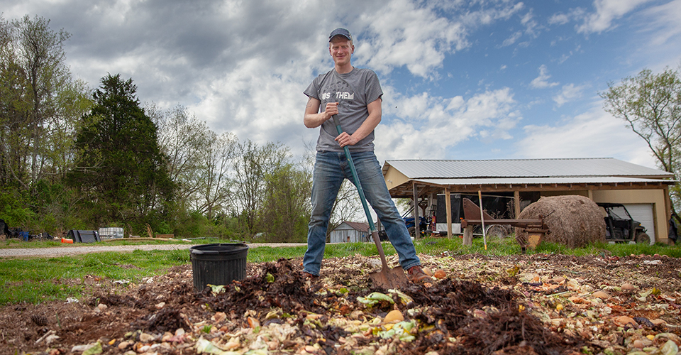 The King of Compost Mountain: Chris Hornsby atop a pile of food waste from Sewanee's McClurg Dining Hall. Photo by Buck Butler