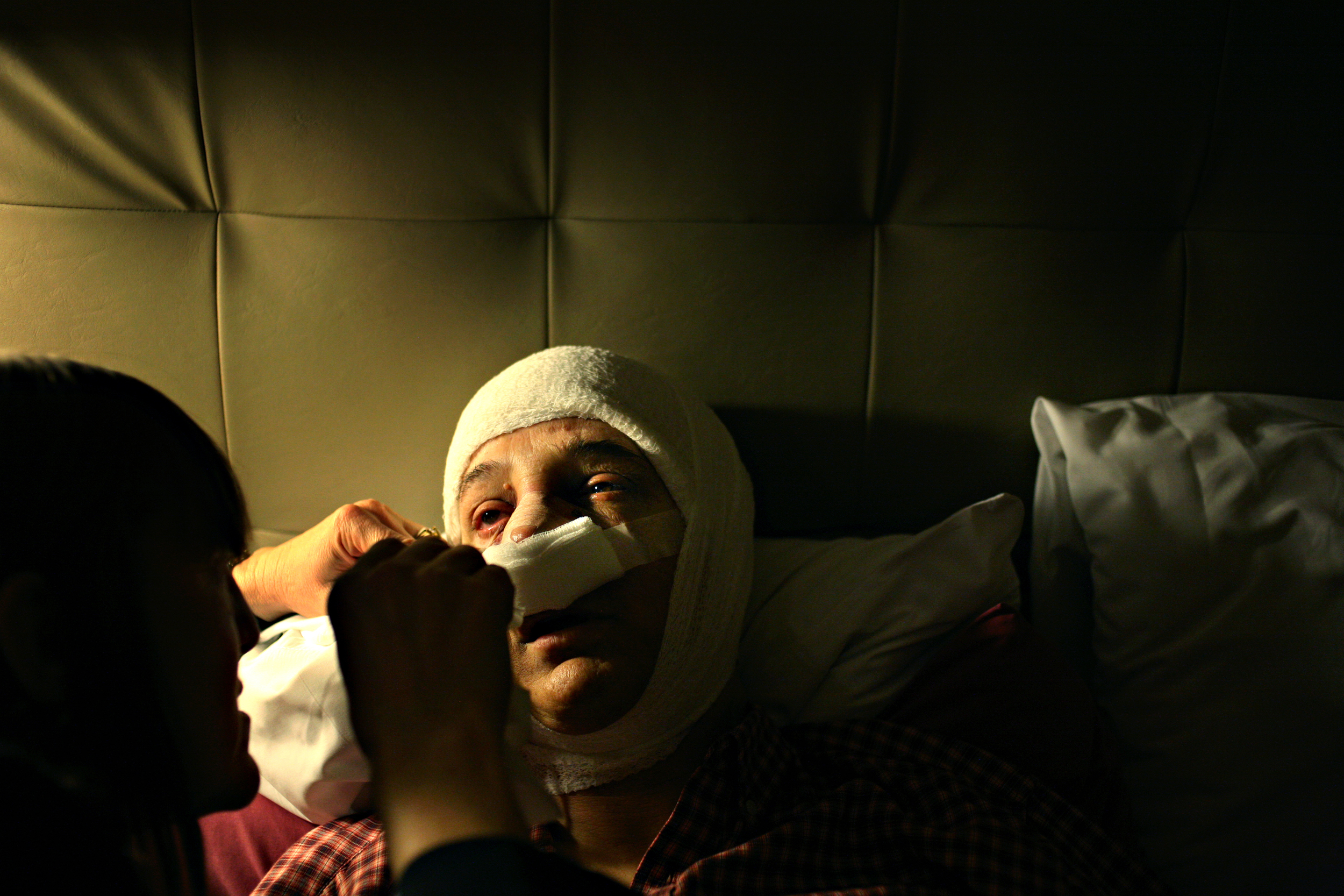 "Elena tries to stay awake as her wife, Zing, changes her bandages after her facial feminization surgery.  In June 2008, Elena and Zing watched a movie,  Ma Vie en Rose , about a Belgian boy coming to terms with his gender identity. The movie triggered a realization in Elena, and soon after she began the process of physically transforming to match her body to how she felt inside.  ""The surgeries were correcting society's misrepresentation of me,"" Elena explains. ""But now I don't have a name for what I am. I just know I'm not a man."""