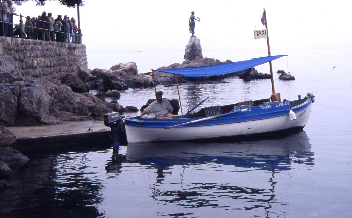 C. Opatija Taxi  It is obvious that this white boat has a dark reflection surrounded by light water.