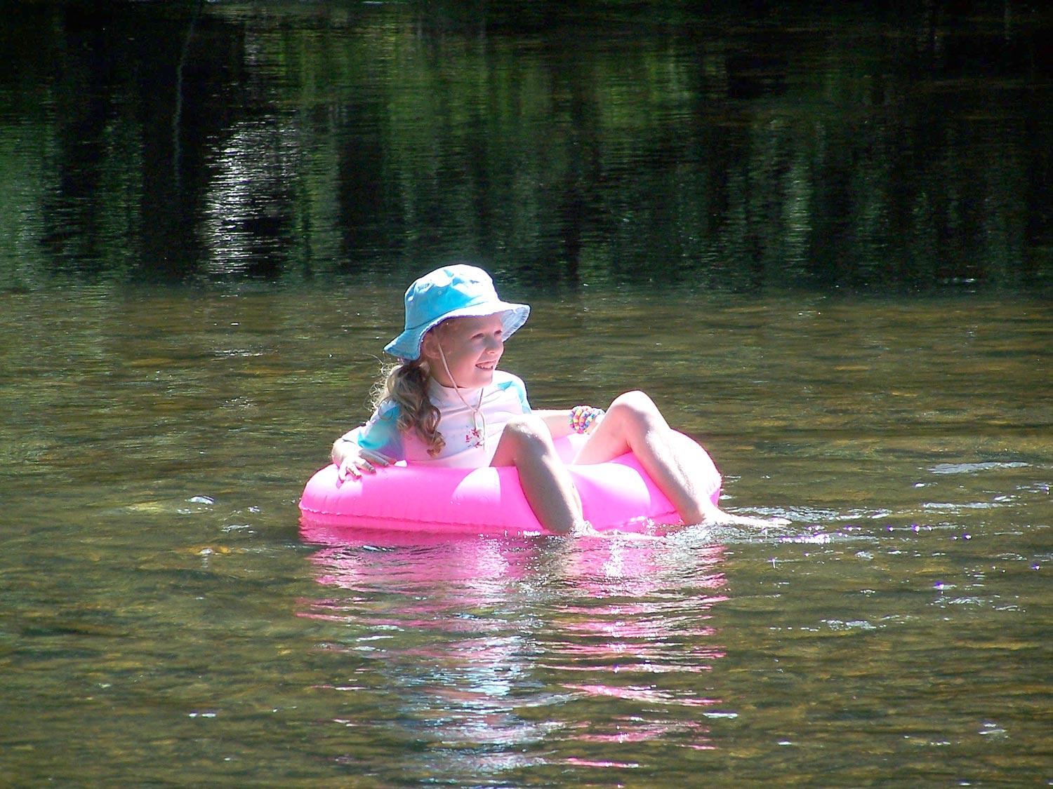 F. Lily  In this photograph the broken reflection of my daughter Lily and her pink float are shown in the river. It can be clearly seen how the reflection alternates between showing the pink float and the trees at the side of the river.
