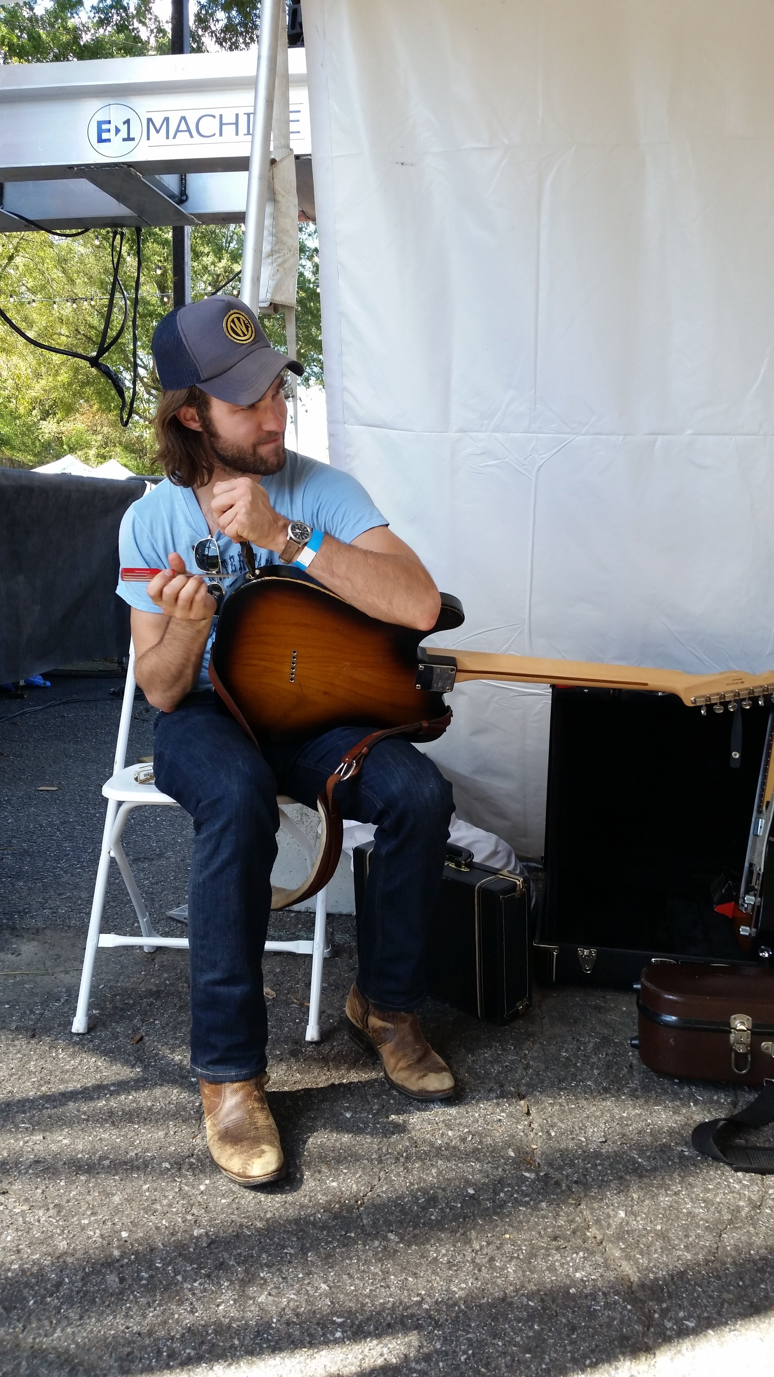 Josh Vana of Nora Jane Struthers & the Party Line works on his guitar backstage